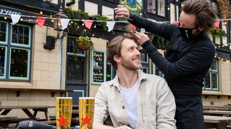 Joe Foyster managed to combine two things that people lacked at a pop-up barber station at the Gregorian Pub in Bermondsey, London.  Barber Michael Douglas makes sure there's a good head on it