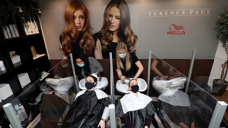 Louise Boothby (L) and Chloe Travis get their hair washed in a salon in Knutsford, Cheshire